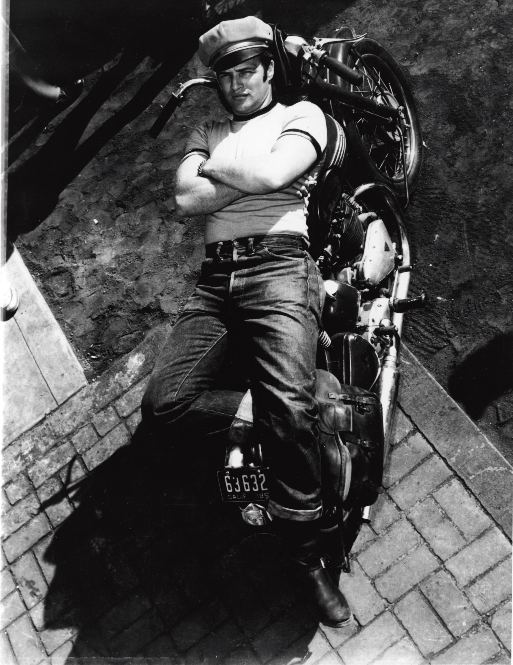 American actor Marlon Brando (1924 - 2004) lies on a motorcycle in a publicity shot for the film 'The Wild One,' directed by Laszlo Benedek, California, 1953. (Photo by Columbia TriStar/Courtesy of Getty Images)
